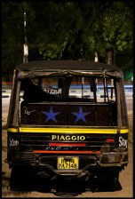 A driver spends the night in his tuk tuk.